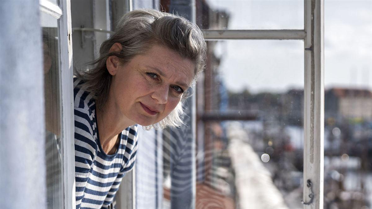 Trine Appel læner sig ud af et vindue