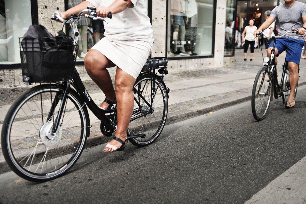 To cykler på en gade, hvor den første er en elcykel