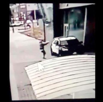 En mand skyder ind gennem en parkerte politvogns ruder