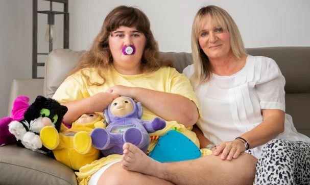 En stor teenager sidder med sin mor i en sofa. Teenageren har en sut i munden og tøjdyr på skødet