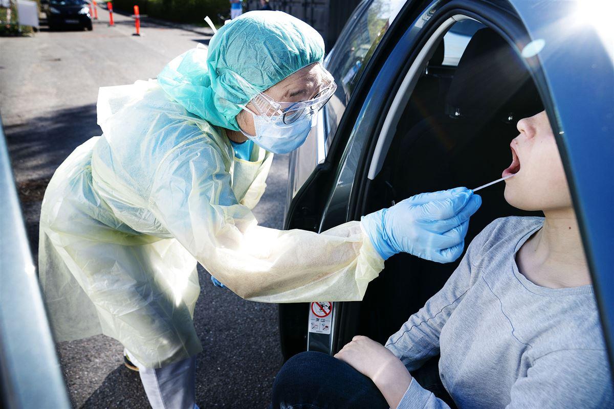 en kvinde i en blå bil bliver corona-testet af en sygeplejerske der er iført engangskittel, engangs handsker, hårbeskyttelse. mundbind og visir.