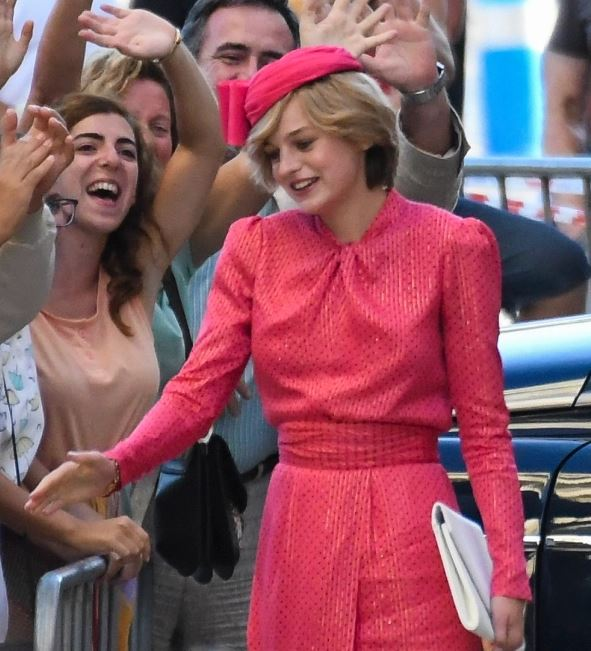 En dame i en rød kjole hilser på en masse mennesker