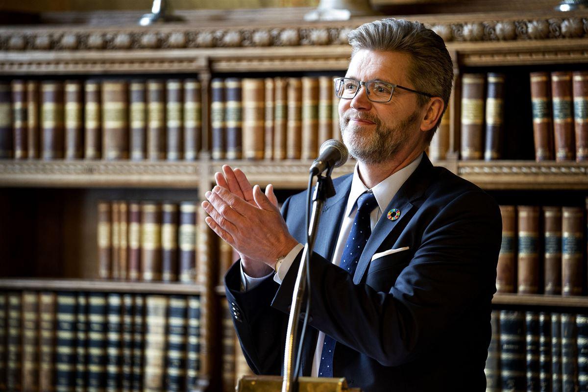 Frank Jensen foran en mikrofon - i baggrunden en reol med gamle bøger