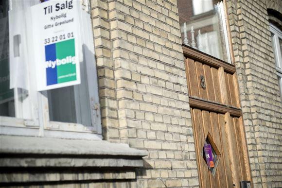 Et til salg skilt hænger i et vindue i en ejendom