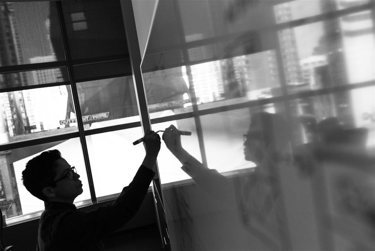 Et sorthvidt billede af en mand foran en tavle taget i modlys