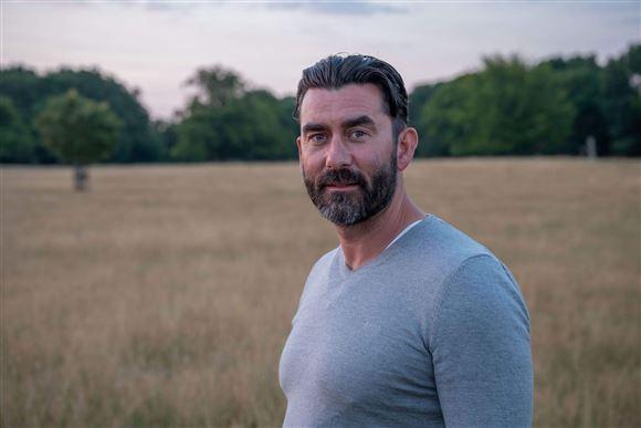 Billede af en mand med skæg og stram sweater i en kornmark