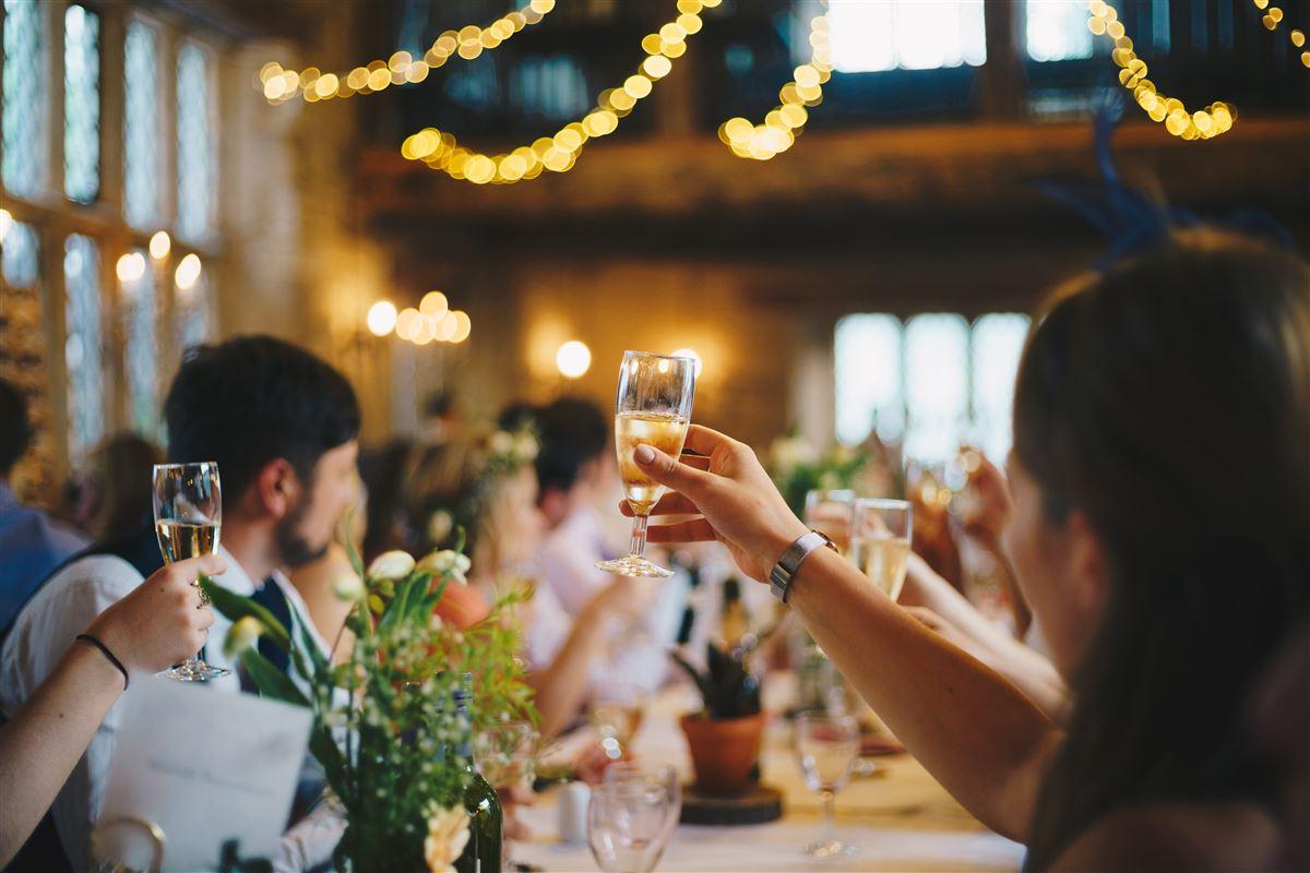 En forsamling skåler i champagneglas efter lyskæderne i loftet og bordpynten at dømme, kunne der være tale om et bryllup.