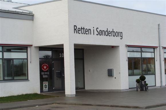 Den hvide bygning hvor retten i Sønderborg har til huse. Der står Retten i Sønderborg med store sorte bogstaver på den hvide facade.