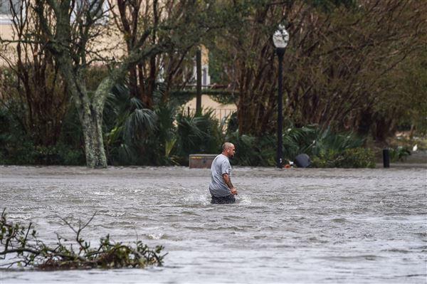 En mand går på oversvømmet gade i Florida efter stormen Sally