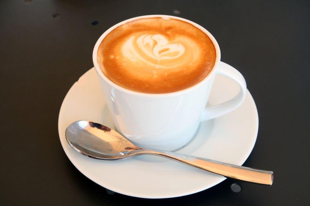kaffekop med kaffe på underkop med teske