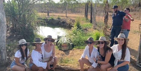 Seks unge kvinder i hatte med en kæmpe krokodille bag dem