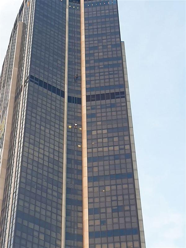 En lille prik viser en mand på vej op ad facaden på en skyskraber
