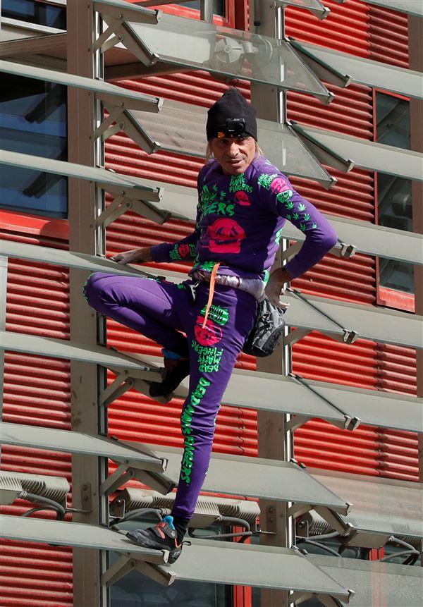 En mand på en facade i tætsiddende kravler-outfit