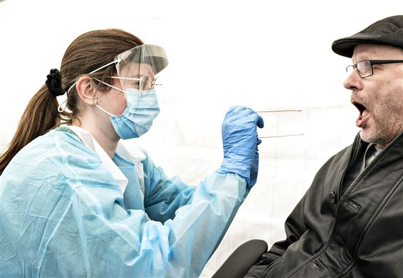 Sygepeljeske tester en mand med åben mund