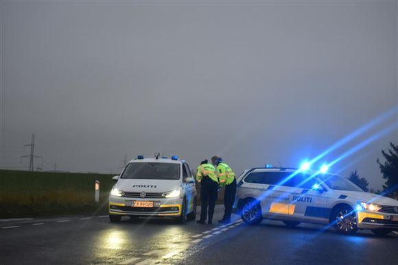 To politibiler med blink spærrer en hovedvej af.