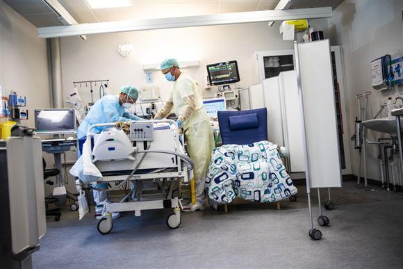 En hospitalsstue, hvor to læger eller sygesplejersker står ved en hospitalsseng med engangskitler, hårnet, handsker og masker på.