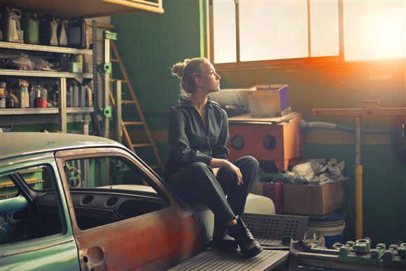 En ung kvinde i arbejdstøj sidder på en gammel bil i en garage