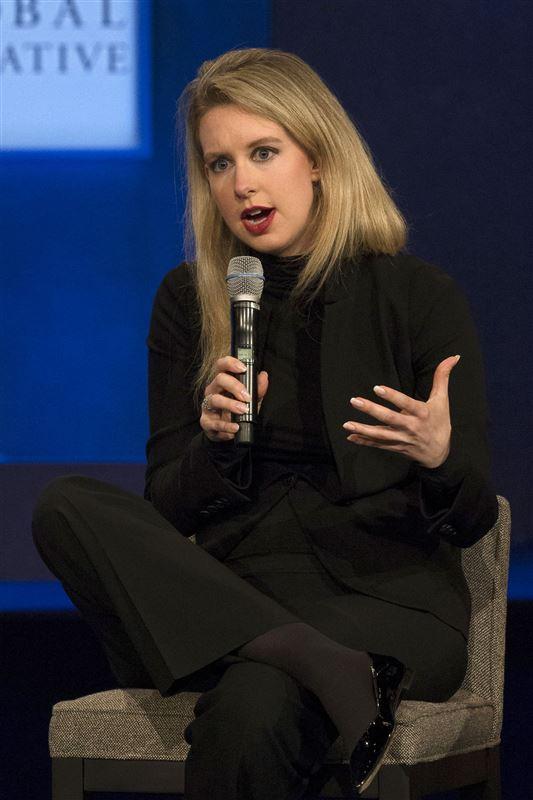 Blond kvinde i sort tøj med en mikrofon i hånden