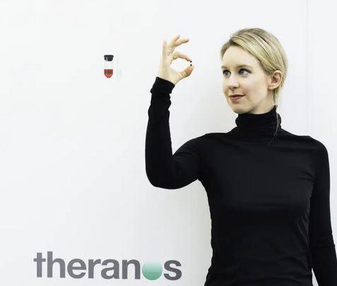 en kvinde med en lillebitte blodprøve mellem fingrene
