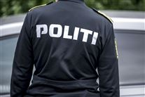 "En politibetjent med ryggen til. Han har en sort jakke på med hvide versaler, hvor der står ""politi""."