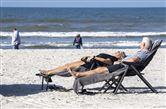 En kvinde og mand ligger i liggestole ved vandet