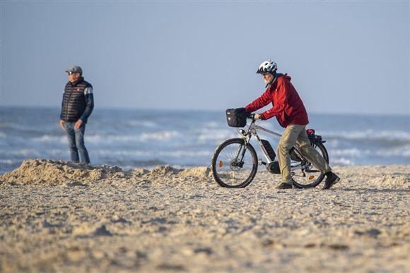 Cyklist på strand i strålende solskin