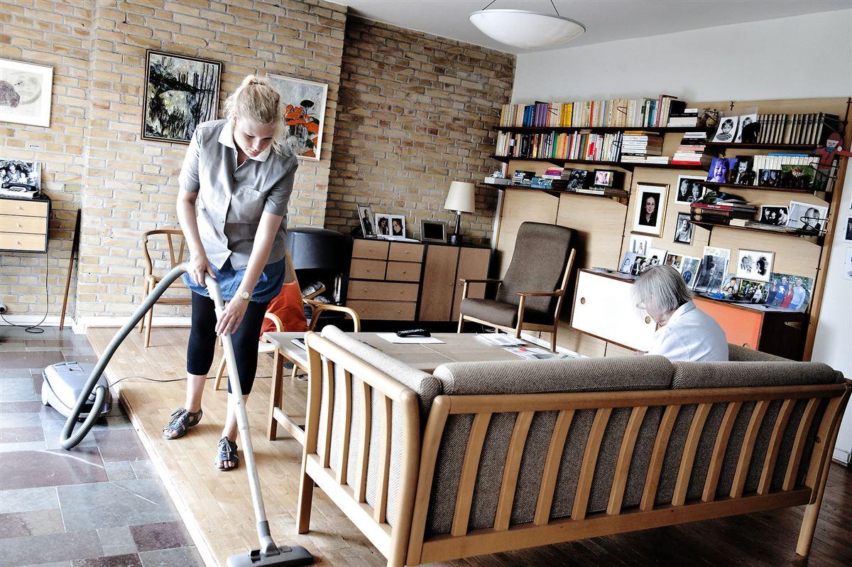 Kvinde gør rent med støvsuger mens ældre dame sidder i sofa