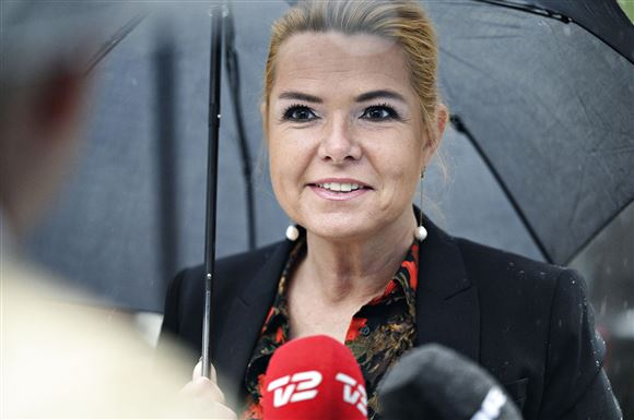 Venstres Inger Støjberg smiler mens hun står under paraply