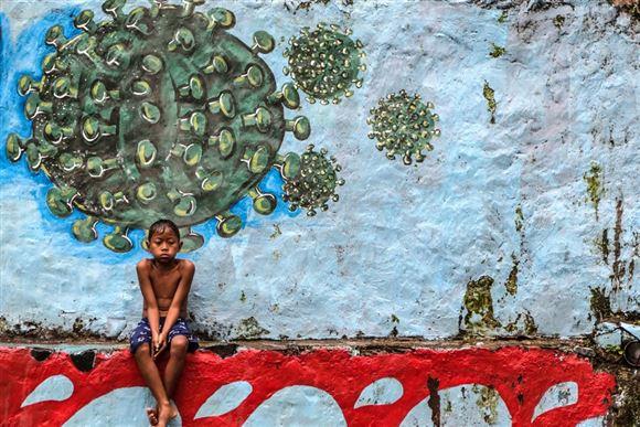 dreng sidder under et murmaleri der forestiller coronavirusset