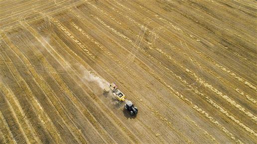 høstmaskiner på mark set fra oven