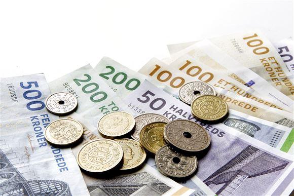 En bunke penge bestående af både sedler og mønter