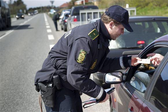 en politibetjent tjekker en bilist med alkoholmeter