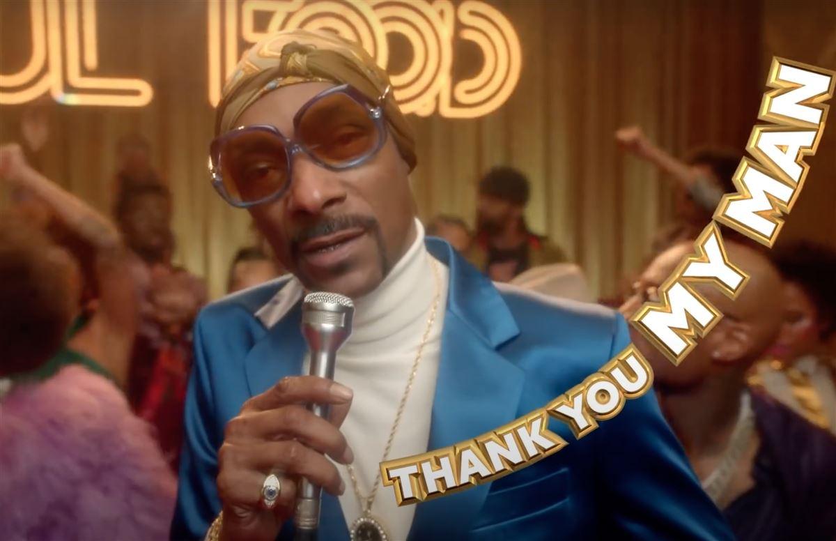 Snoop Dogg med hvis rullekrave, blå blazer og solbriller danser og synger