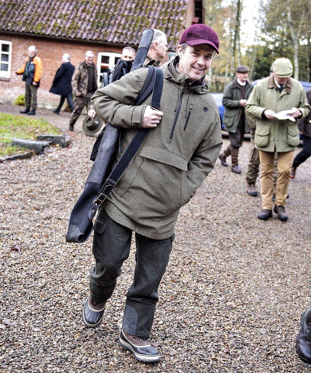 Kronprins Frederik i jagttøj, med gevær over skulderen og en mørkelilla kasket på