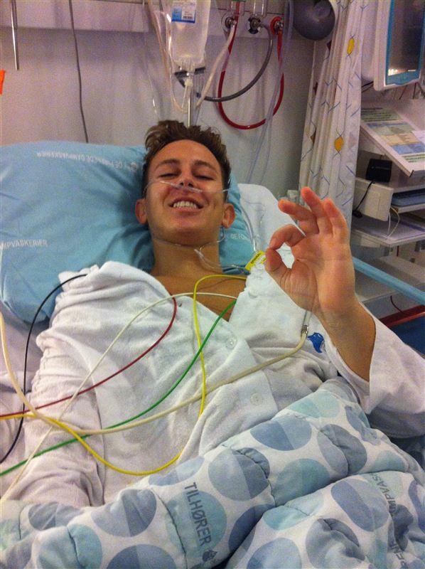 En ung mand i en hospitalsseng med slanger overalt.