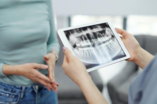 En patient kigger på et røntgenbillede af nogle tænder