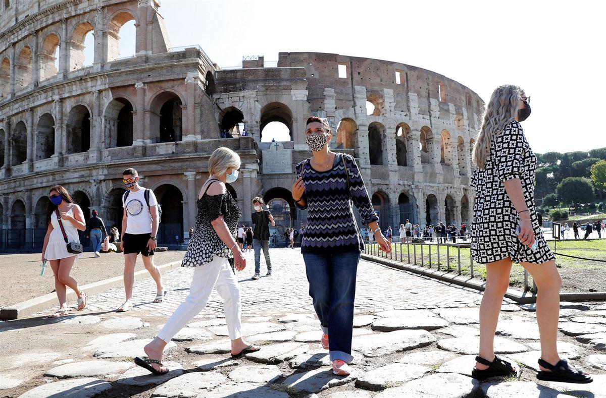 Turister med mundbind går foran Colosseum