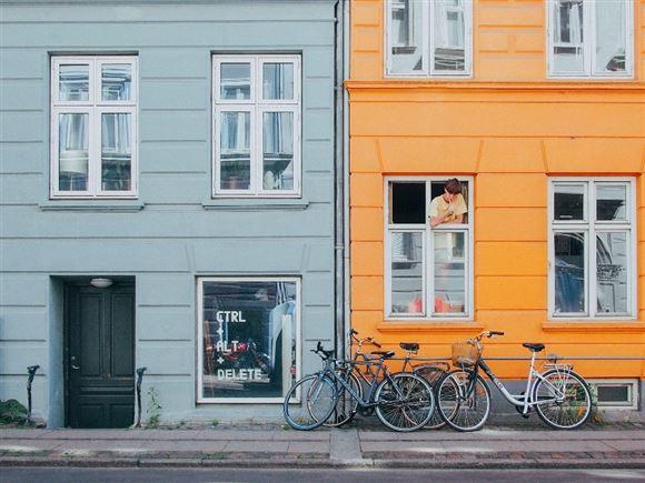 En gade i København med en unge, der kigger ud af et vindue