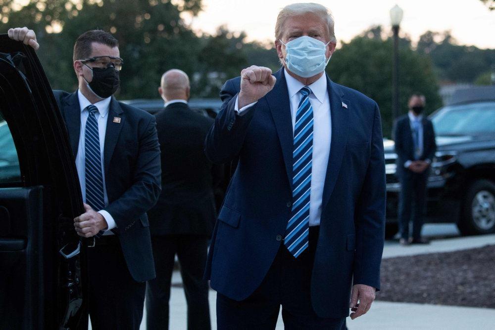 Donald Trump med ansigtsmaske omgivet af sikkerhedsfolk