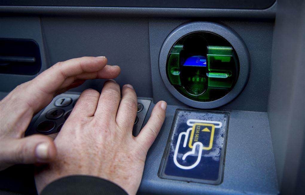 personer står ved pengeautomat