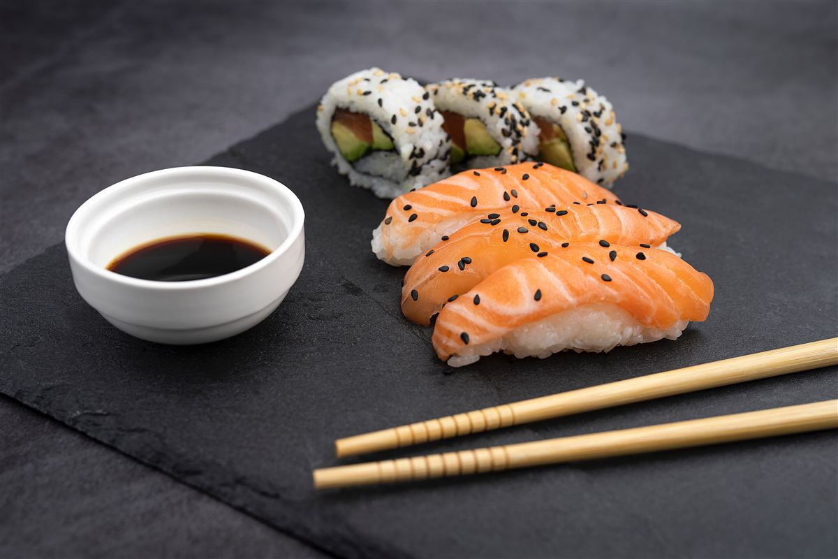 sushi, spisepinde og soyasauce anrettet på bræt