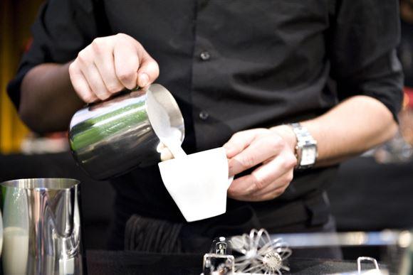 mand hælder mælk fra kande i kaffekop