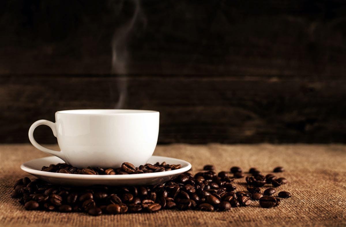 rygende kaffekop på underkop omgivet af kaffebønner