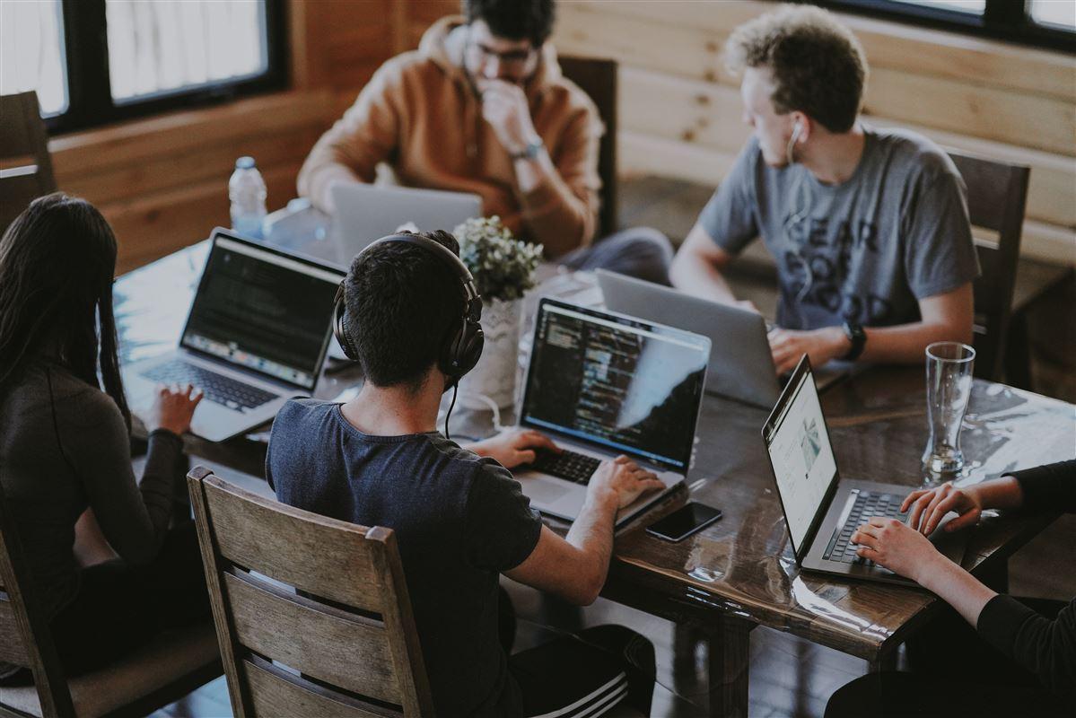 fire personer sidder med computere ved et bord