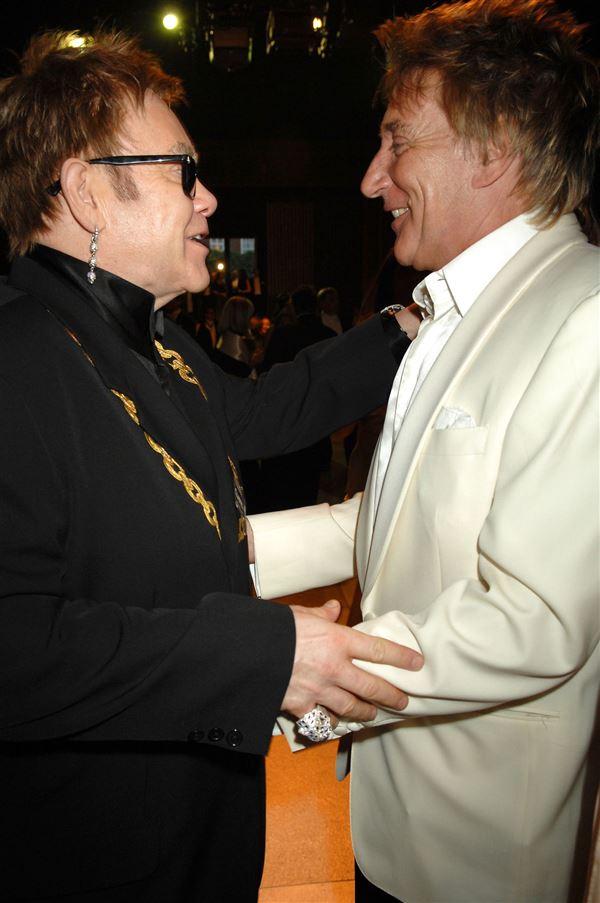 Elton John i mørket jakkesæt står og holder om Rod Stewart i hvidt jakkesæt.