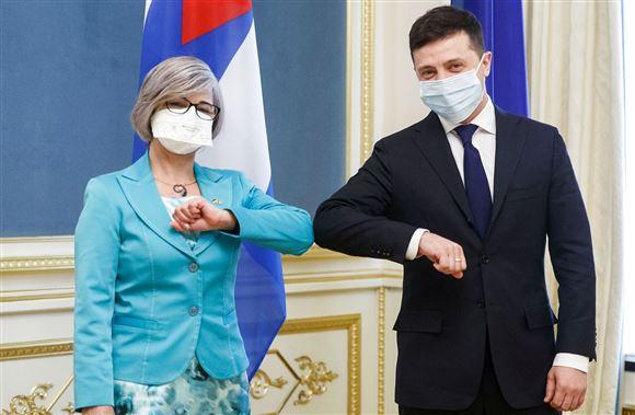 to personer med ansigtsmaske hilser med albuen