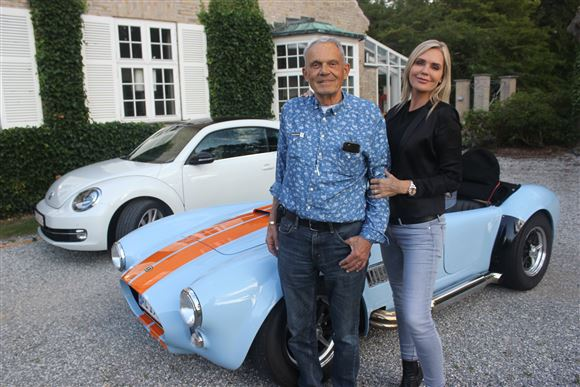 Janni og Karsten foran et stort hus med VW og Cobra-biler bag dem