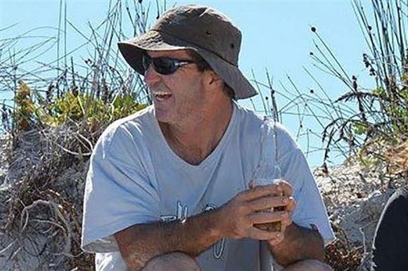 En smilende mand på en strand med en bøllehat på