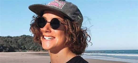 En smilende langhåret teenager med baseballkasket og solbriller