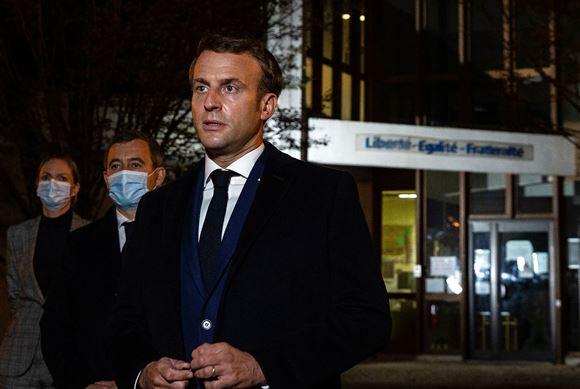 Billede af Macron og nogle andre mænd foran en lille skole